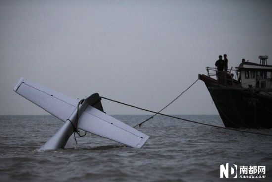 坠海的飞机已经被救援队用绳索固定,但因为海水过浅,只能暂时停放在原地。