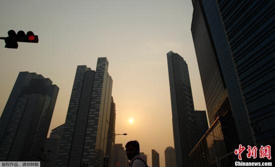 当地时间2013年6月18日,受印度尼西亚森林火灾的影响,邻国新加坡被烟雾和阴霾笼罩。当地政府建议人们尽量减少户外活动。图为新加坡商业中心区笼罩在浓雾之下。