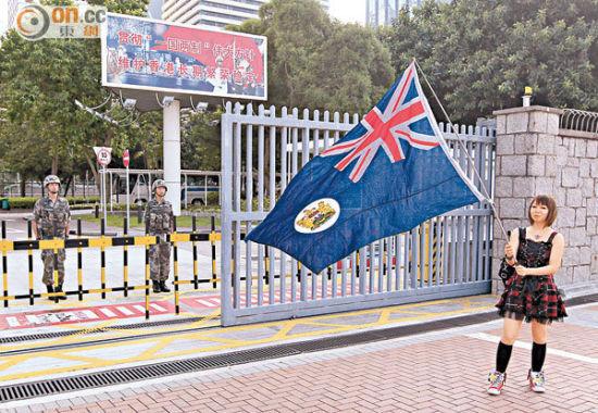 一名30岁姓谢的女成员在军营前展示并挥动港英旗帜。