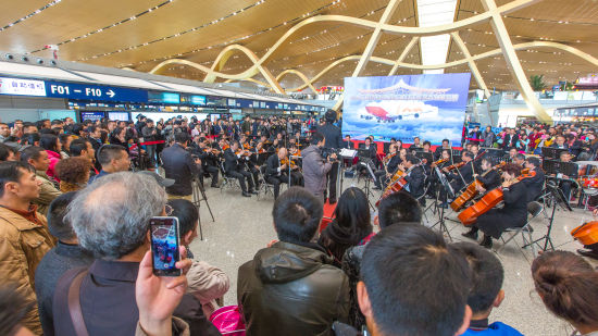 """乘客们在欣赏""""中国梦・长水情""""交响音乐演奏文艺展演。"""