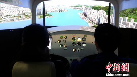 12月15日,飞行爱好者在专业机师指导下亲手操作模拟飞行训练器。韦杰夫 摄