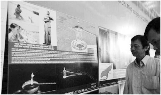 """越南市民观看一个刻画英雄母亲形象的""""黄沙英雄纪念碑""""的设计方案。"""