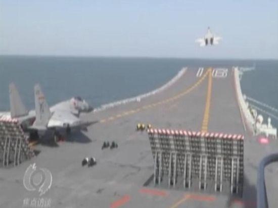 5月2日,中央电视台《焦点访谈》节目聚焦中国航母辽宁舰,曝光了辽宁舰连续放飞歼-15舰载机的画面。图为两架歼-15舰载机在辽宁舰航母上准备起飞。(来源:CCTV)