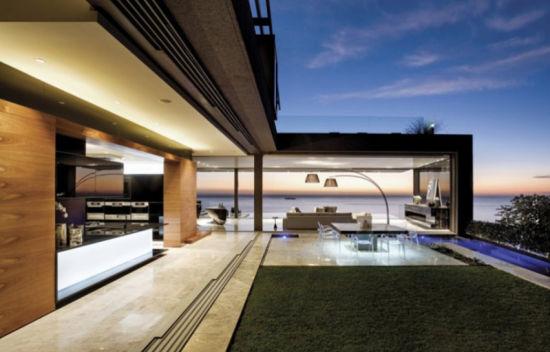 别墅正面与周围的山脉颜色相适应,还加入了铝制结合,给人以坚固耐久的印象,同时,还安装了许多百叶窗、屏风等结构。住宅内部主要使用了胡桃木、黑色大理石和玻璃材料,给人温和舒适的观感。客厅东西方向可以完全开放,形成一个类似开放式露台的空间。别墅细节精致独特,圆形的门厅被胡桃木包围,是房间内部独具特色的部分,优雅的悬空式楼梯更加突出了奢华气氛。室内还有背光式玻璃等结构,独特的照明设备更加凸显了整体效果。