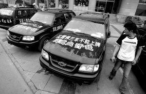 车主们将不能上牌照的新车停在亚运村附近展示。本报实习生