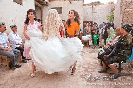 新娘盖着头巾在伴娘的搀扶下,嫁出去了(谢光辉摄)