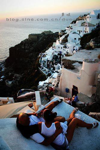 情侣在崖边洞穴的屋顶等待日落爱琴海