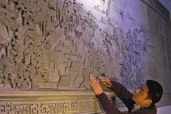 蔡云娣在自己的砖雕作品《姑苏繁华图》前凝神良久,小小的刻刀一点点剔出了细节