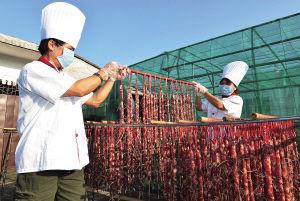 澄迈县瑞溪镇陈奇腊味店的工人正在晾晒腊肠。海南日报记者 王凯 摄