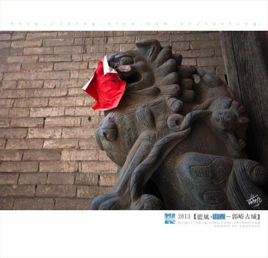 这些门前的石狮子过年的时候为什么要用红纸贴到嘴上,是怕它咬人吗