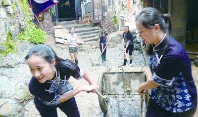 18日,凤凰古城讲解员付思瑞(左一)和吴翠正拖着一车淤泥上坡。