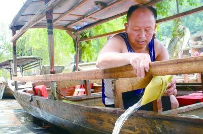 18日下午,田全友在清理船舱。这艘船在洪水来临时救出了35人。
