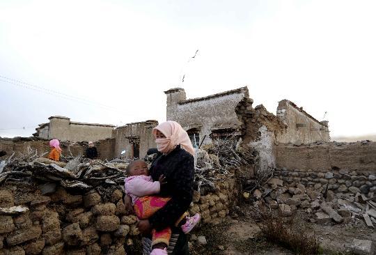 10月6日,西藏当雄县羊八井镇格达乡格达村的一名牧民带着孩子从倒塌的房前走过。新华社记者普布扎西摄