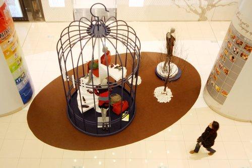 """2008年11月26日,""""鸟笼""""造型的服饰展柜吸引顾客驻足观看"""