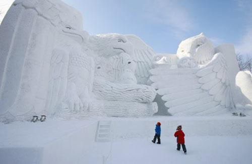 """2月7日,在日本第60届札幌冰雪节上,两名小男孩在名为""""北方森林动物家族""""的雪雕前驻足。"""