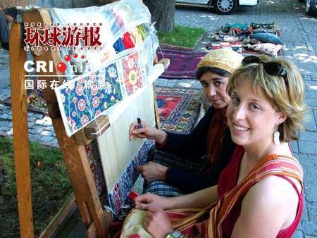 游客和编织地毯的妇人