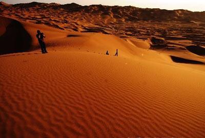 3月27日,摄影爱好者在新疆鄯善县库木塔格沙漠公园拍摄沙漠美景。