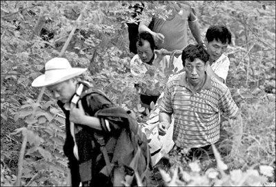 救援人员将死者抬下山。本报记者 吴平 摄