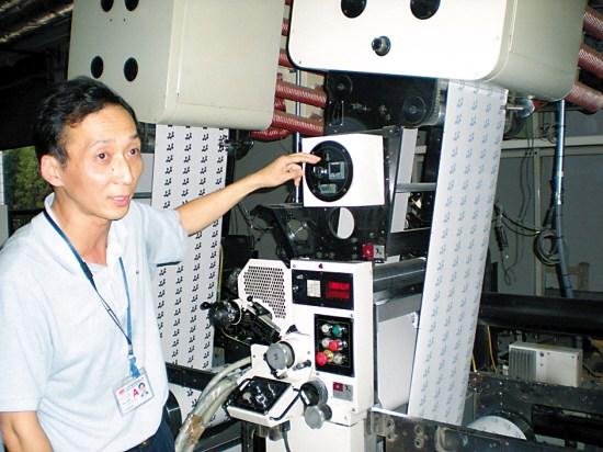 裴航总经理向记者介绍彩票印制的过程