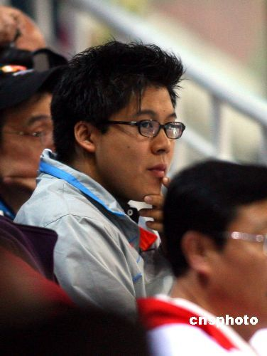 多哈亚运会跳水女子双人三米板决赛,中国选手郭晶晶、李婷获得金牌。霍启刚在看台上身穿中国队运动服观看比赛。