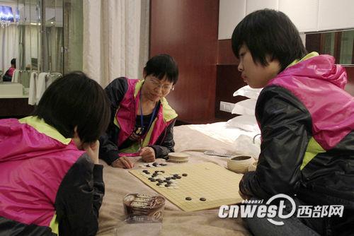 孔祥明在酒店房间为陕西众源围棋队两名小棋手复盘指导。