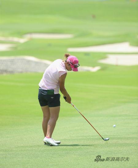 7、击球瞬间:球杆继续下行,重心到左脚,右脚跟抬起,杆头释放,击中高尔夫球。
