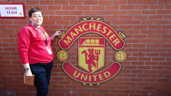 张阿姨在曼联队徽前合影