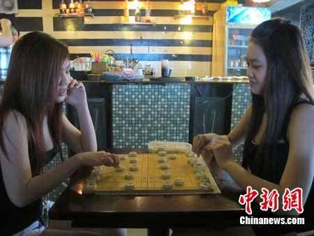 图为越南胡志明市的两位西贡小姐在咖啡店兴致勃勃地下中国象棋。 韩胜宝 摄
