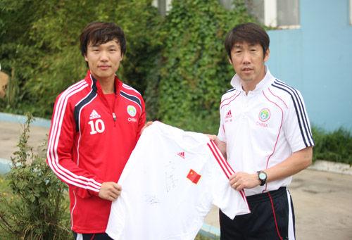 高洪波和邓卓翔展示国足球衣