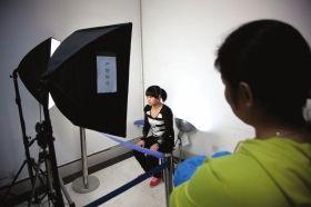 赵常玲坐在灯架前拍摄身份证照片。图/记者辜鹏博