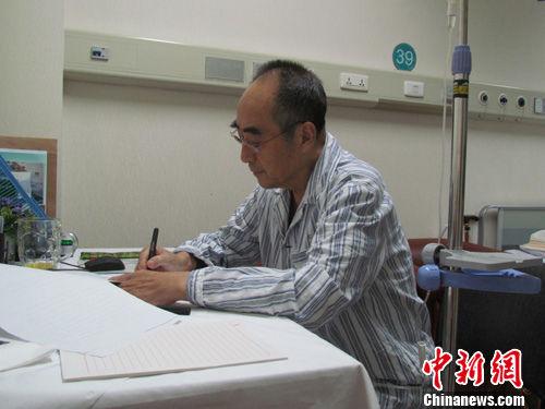 """已是癌症晚期的中国乒坛宿将庄则栋,在住院的危重病房里将""""自己最后一本新书《祖国在我心中》""""定稿。佐佐木敦子摄"""