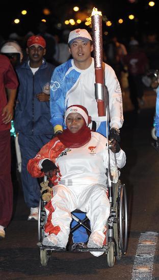 图文-圣火传递在马斯喀特举行 残疾女运动员持祥云