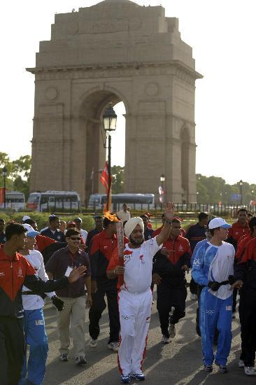 图文-北京奥运圣火在新德里传递 火炬手在印度门前