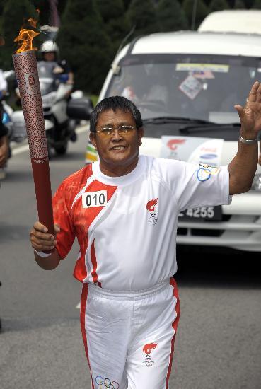 图文-奥运圣火在吉隆坡传递 火炬手向群众致意