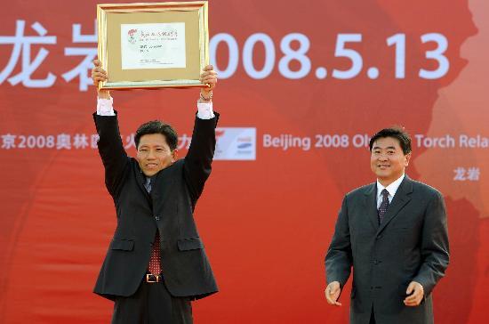 图文-北京奥运圣火在龙岩传递 高举火炬传递城市证书