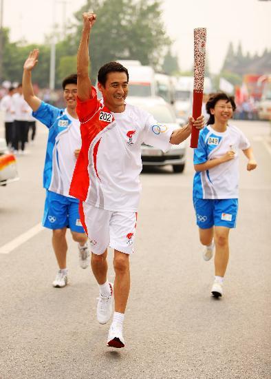 图文-奥运圣火上海次日传递 梁家辉难掩兴奋表情