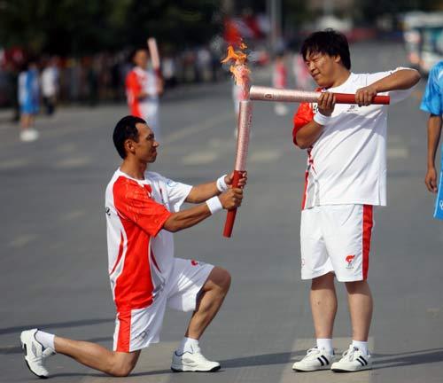 图文-北京奥运圣火在喀什传递 跪地点燃火炬