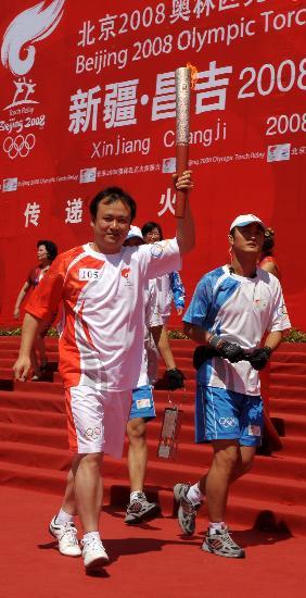 图文-奥运会圣火在新疆昌吉传递 李文杰手持火炬