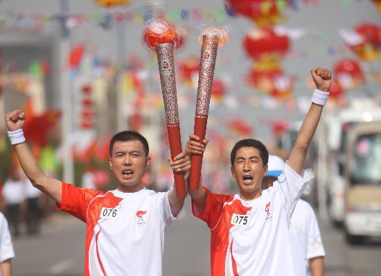 图文-奥运圣火在吴忠传递 火炬手马旭与冯军交接