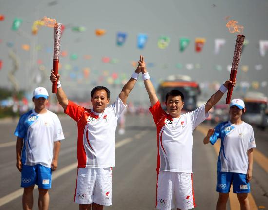 图文-奥运圣火在银川传递 火炬手齐宁与李涛交接