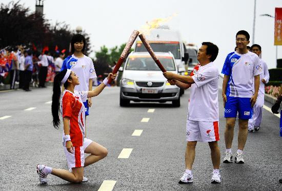 图文-奥运圣火在大连传递 孙嘉艺单膝跪地交接