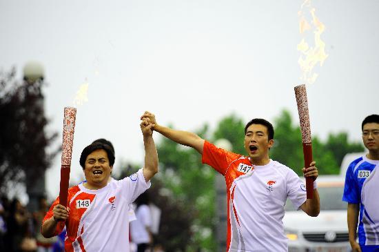 图文-北京奥运圣火在大连传递 哥俩儿紧握拳头