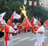 图文-奥运圣火在泰安传递 梁吉银与孙天宝交接火炬
