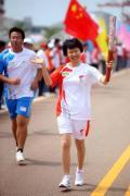 图文-奥运圣火在唐山传递 火炬手身后五星红旗招展