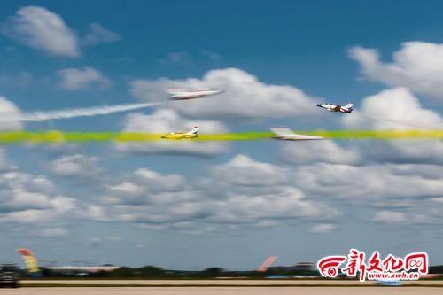 四架飞机拉着彩带交叉飞行.