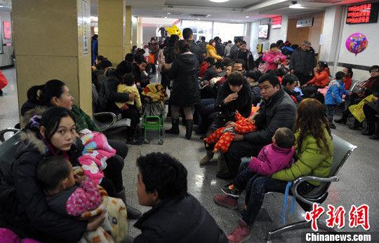 12月5日,在河北省儿童医院呼吸科大厅内,坐满了抱着孩童前来看病的父母。中新社发 翟羽佳 摄