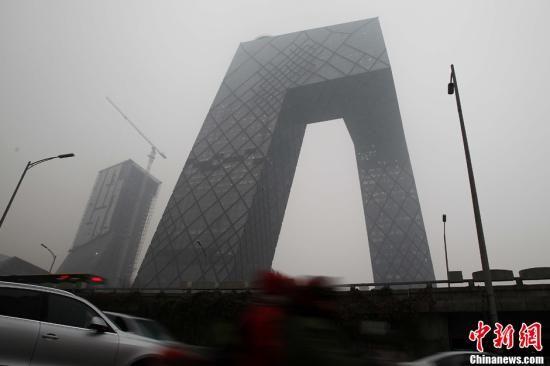 12月5日,中央气象台再次发布大雾蓝色预警,华北、江淮、黄淮等地有轻雾,局部能见度不足200米。图为雾中的央视大楼新址。中新社发 富田 摄